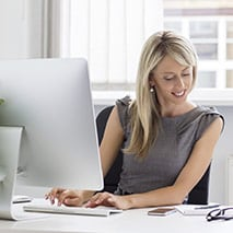 Woman looks at notes while typing on an iMac computer